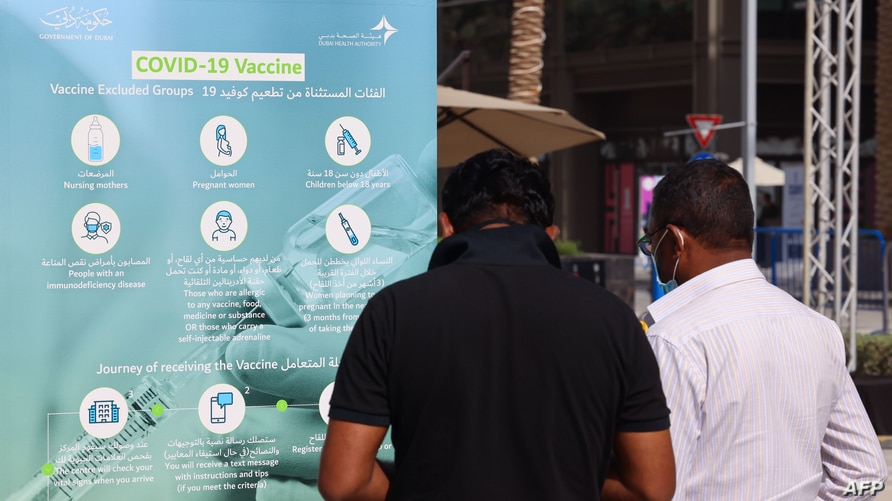 People look at an information placard in front of a designated COVID-19 vaccination center at Dubai's financial center district…