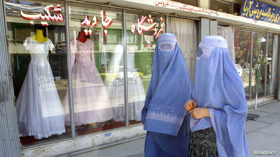 FILE - Afghan women walk past a shop specialising in wedding dresses in Kabul.