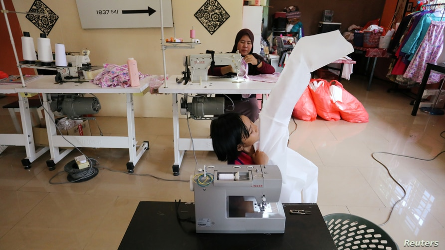 Nur Afia Qistina Zamzuri, a 9-year-old girl sews personal protective equipment (PPE) for free to medical workers working in…