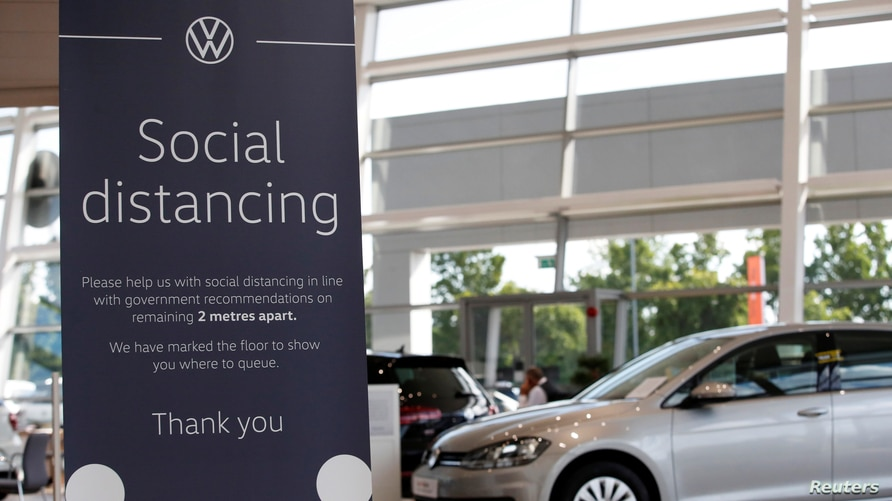 A social distancing sign is seen at a Marshall Volkswagen car dealership, following the outbreak of the coronavirus disease …