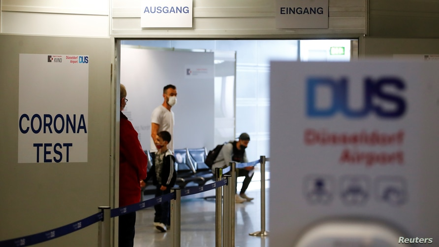 Travellers line up at the new Corona Test Centre at Duesseldorf Airport in Duesseldorf, Germany, July 27, 2020. Travellers can…