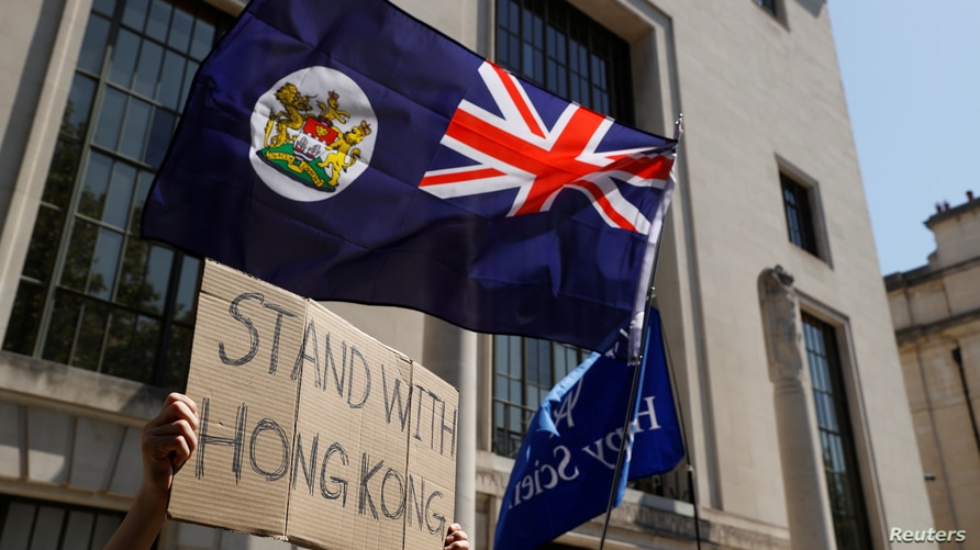 A flag of Hong Kong is waved in front of a placard during a protest against Hong Kong's deteriorating freedoms outside China's…