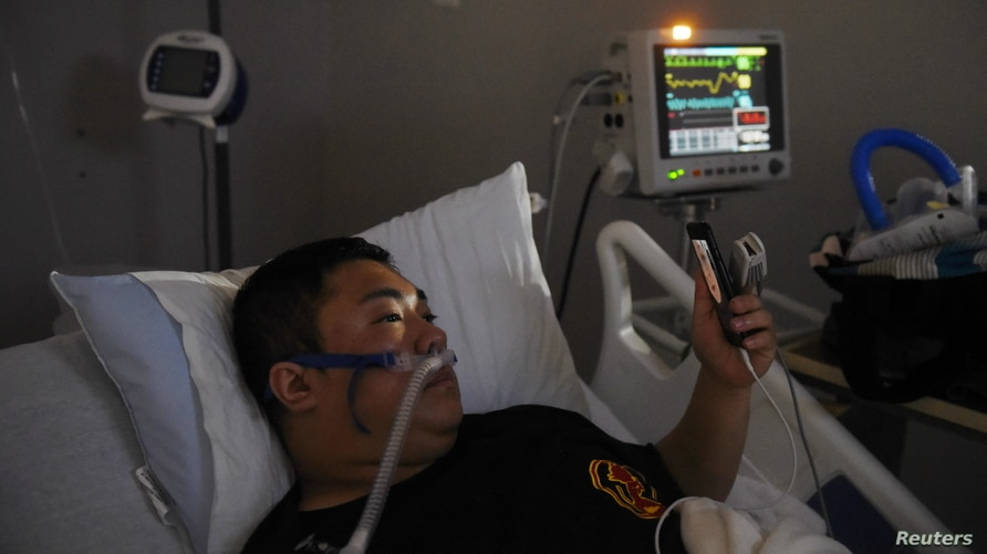 Duc Nguyen speaks with his wife using FaceTime on New Year's Day from inside the coronavirus disease (COVID-19) unit at United Memorial Medical Center in Houston, Texas, U.S., Jan. 1, 2021.