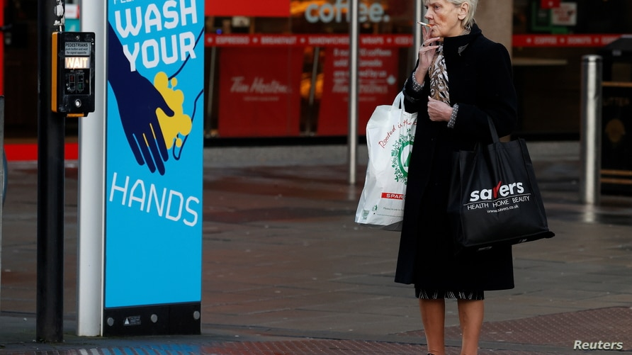 A woman smokes a cigarette as she stands by a sign encouraging people to wash their hands amid the outbreak of the coronavirus…