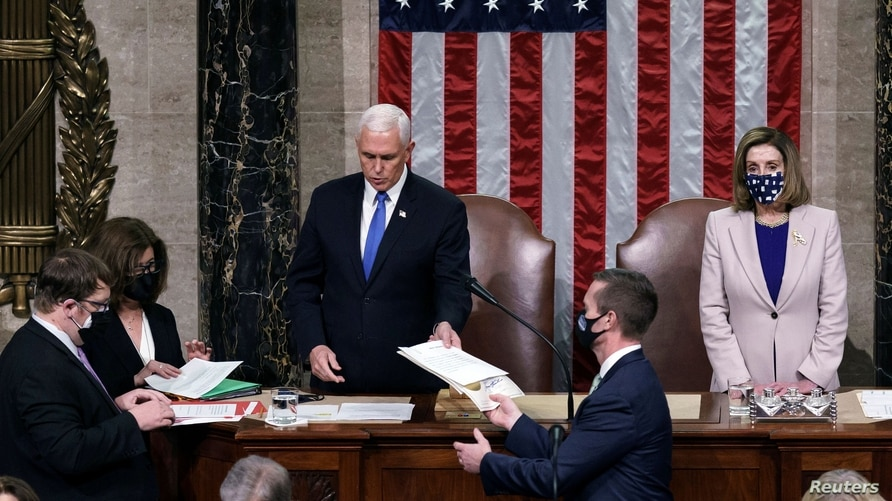 U.S. Vice President Mike Pence hands the West Virginia certification to staff as Speaker of the House Nancy Pelosi looks on.