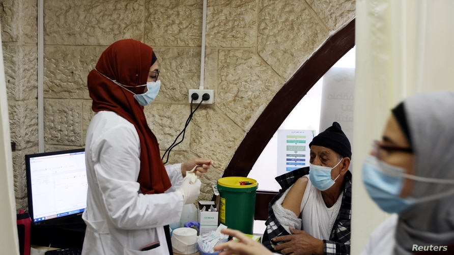An Arab medical worker prepares to vaccinate a man against the coronavirus disease (COVID-19) as Israel continues its national vaccination campaign amid a third COVID-19 lockdown, in East Jerusalem, Jan. 7, 2021.