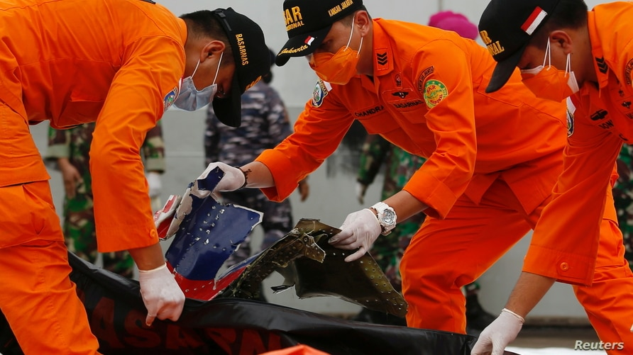 Indonesian rescue members inspect what is believed to be the remains of the Sriwijaya Air plane flight SJ182, which crashed…