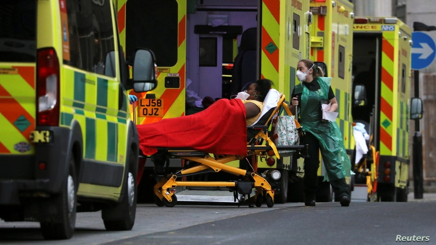 Medical workers transport a patient from an ambulance at the Royal London Hospital amidst the spread of the coronavirus disease…
