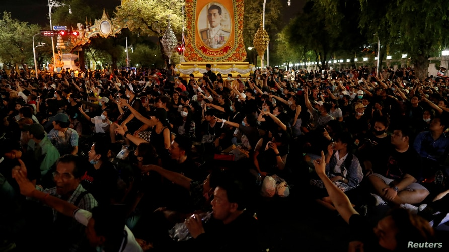 FILE - Pro-democracy demonstrators stand in front of a portrait of Thailand's King Maha Vajiralongkorn outside the Government House during an anti-government mass protest, on the 47th anniversary of the 1973 student uprising, in Bangkok, Thailand, Oct. 14, 2020.