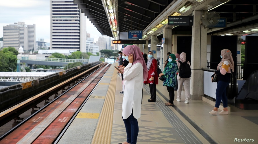 People wait for a Light Rail Transit train at a station, during a lockdown due to the coronavirus disease (COVID-19) outbreak, in Kuala Lumpur, Malaysia, Jan. 14, 2021.