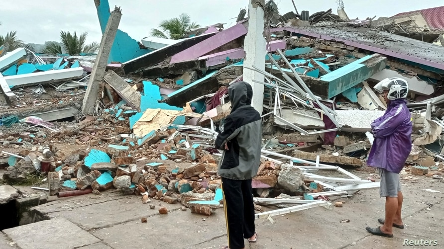 People look at a damaged hospital building following an earthquake in Mamuju, West Sulawesi province, Indonesia, January 15,…
