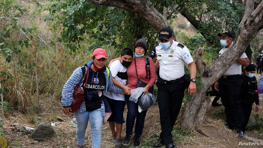 Honduran migrants are accompanied by a police officer after Guatemalan security forces cleared a road where the…