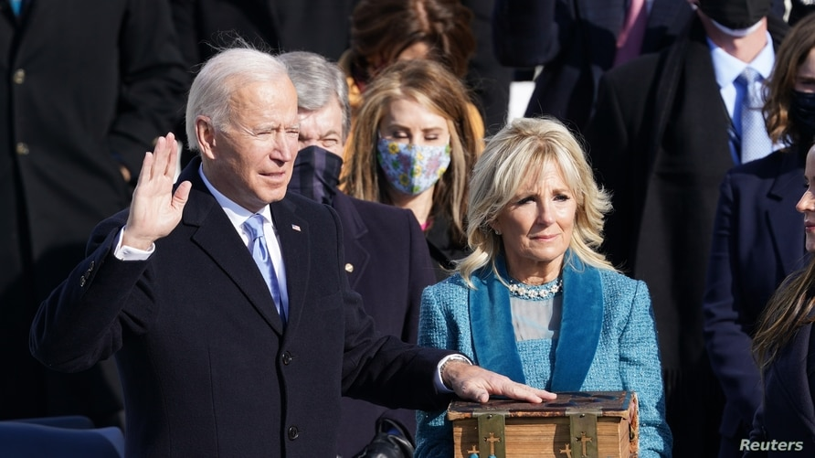 Joe Biden is sworn in as the 46th President of the United States as his wife Jill Biden holds a bible.
