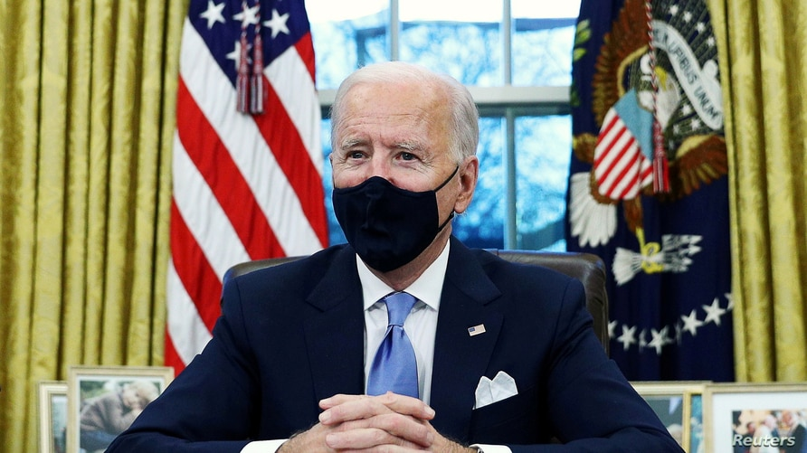 U.S. President Joe Biden signs executive orders in the Oval Office of the White House in Washington.