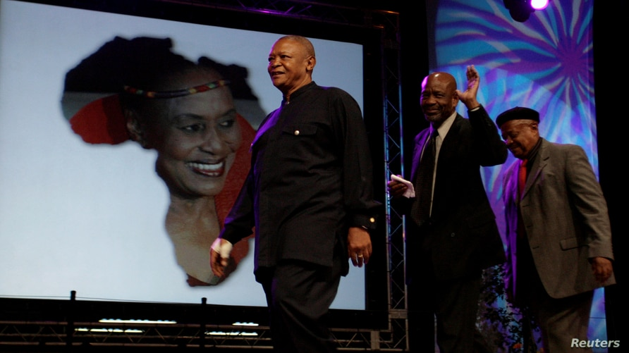 FILE - Trombonist and composer Jonas Gwangwa, right, walks on stage trumpeter Hugh Masekela (L) and Caiphus Semenya after paying tribute during Miriam Makeba's memorial service in Johannesburg November 15, 2008.