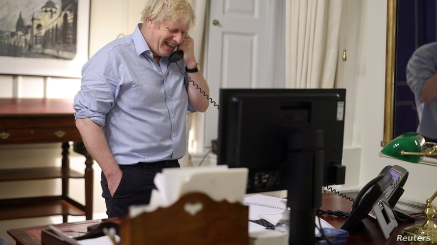 British Prime Minister Boris Johnson speaks to U.S. President Joe Biden from London, Britain in this social media image…