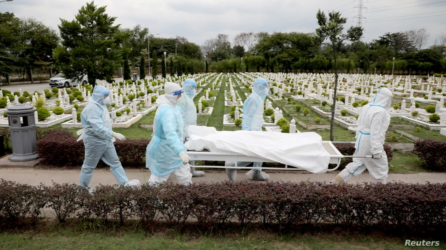 Workers wearing personal protective equipment (PPE) carry the body of a victim of the coronavirus disease (COVID-19) at a…