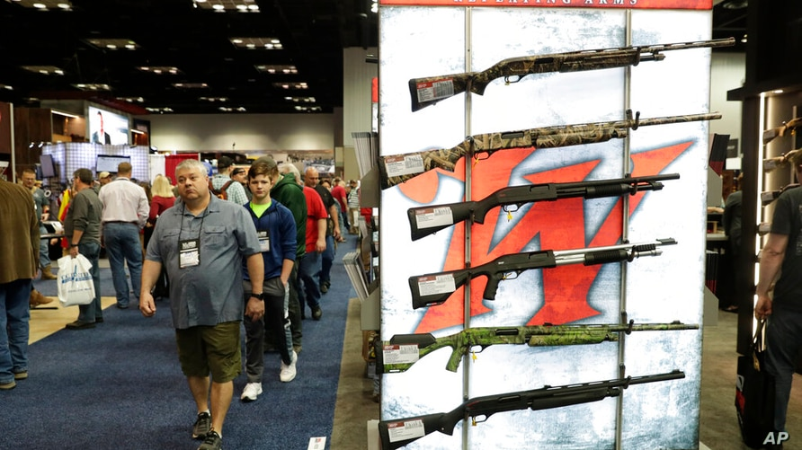 Gun enthusiasts walk through the gun displays in the exhibition hall at the National Rifle Association Annual Meeting in…