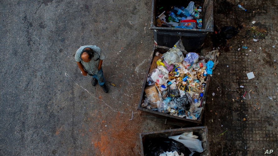 A homeless man walks next to trash dumpsters in Beirut, Lebanon, Sunday, July 12, 2020. Lebanon should quickly form a reform…