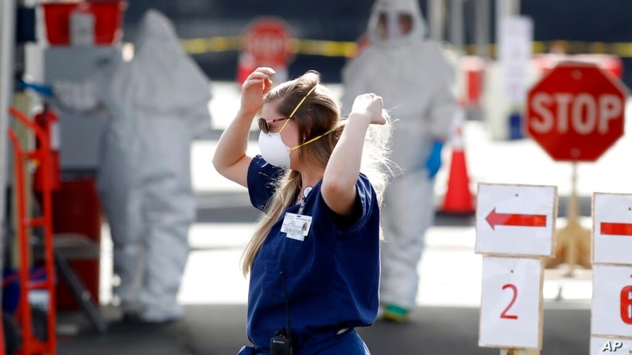 In this Friday, March 13, 2020 file photo, Medical University of South Carolina project manager Amy Jackson adjusts her face…