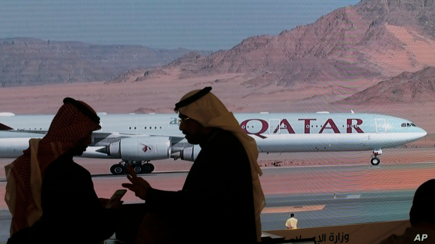 Journalists chat as video of a plane carrying Qatari Emir Sheikh Tamim bin Hamad Al Thani is shown on a screen while landing at…