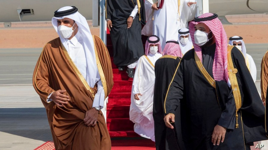 In this photo provided by the Saudi Royal Court, Saudi Arabia's Crown Prince Mohammed bin Salman, right, welcomes Qatar's Emir.
