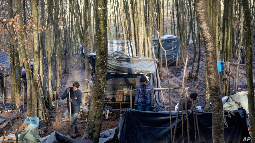 Migrants put up shelter improvised from plastic sheets and tree branches at a makeshift camp in a forest outside Velika Kladusa…