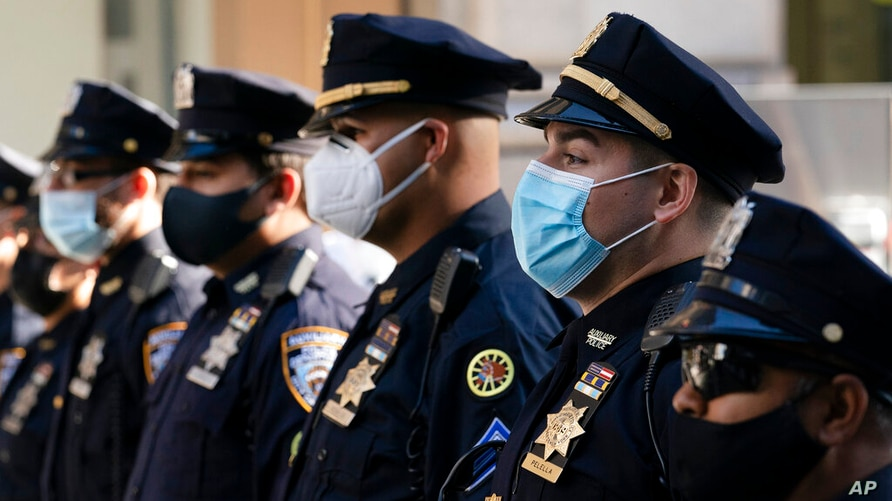 FILE - In this= Oct. 5, 2020, file photo, New York Police Department officers in masks, stand during a service at St. Patrick's…