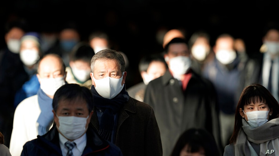 A station passageway is crowded with commuters wearing face mask during a rush hour Friday, Jan. 8, 2021 in Tokyo. Japanese…