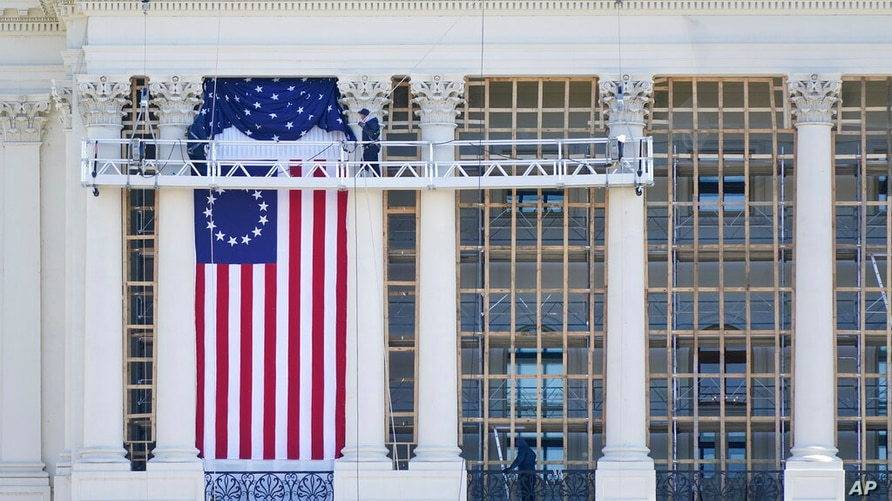 Workers install a flag on the West Front of the U.S. Capitol as preparations take place for President-elect Joe Biden's…
