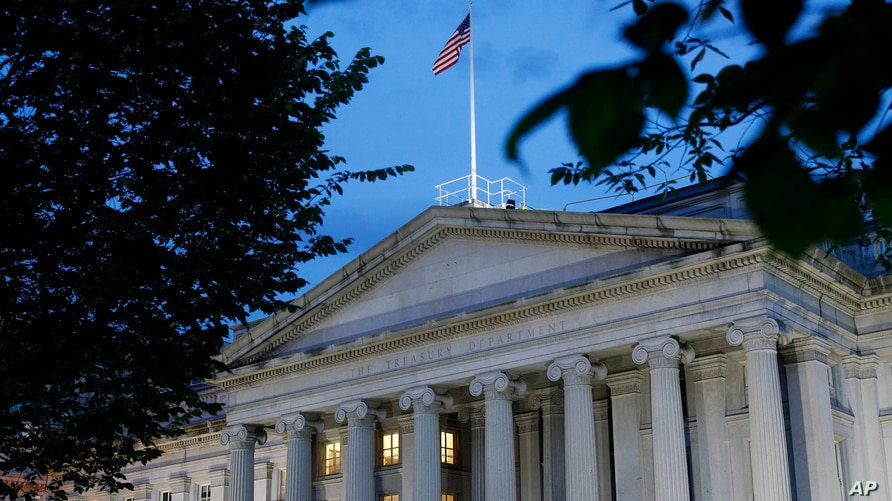 FILE - This Thursday, June 6, 2019 file photo shows the U.S. Treasury Department building at dusk in Washington. The Corporate…