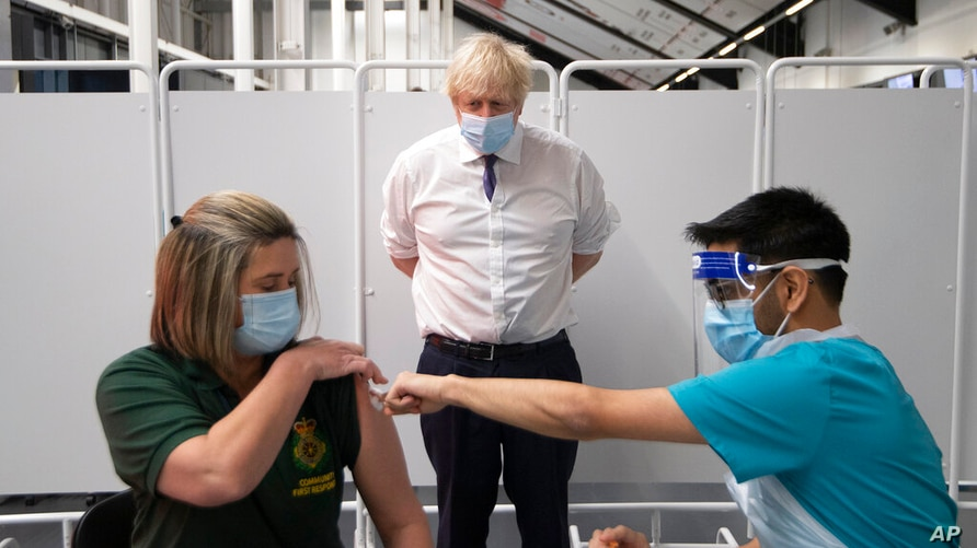 Britain's Prime Minister Boris Johnson watches first responder Caroline Cook receiving an injection of a Covid-19 vaccine at…