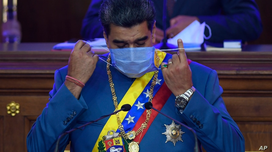 Venezuelan President Nicolás Maduro removes his mask as he prepares to speak about his annual report to the nation before legislators in the National Assembly, Caracas, Jan. 12, 2021.