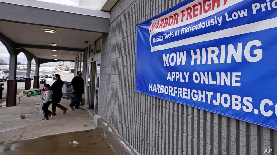 "FILE - In this Dec. 10, 2020, file photo, a ""Now Hiring"" sign hangs on the front wall of a Harbor Freight Tools store in…"