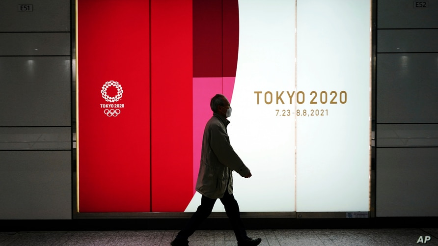 A man wearing a protective mask to help curb the spread of the coronavirus walks near a banner of the Tokyo 2020 Olympics at an…
