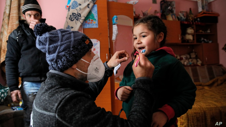 A little girl gets help from Valeriu Nicolae to learn brushing his teeth correctly as her father watches n Nucsoara, Romania, Jan. 9, 2021.