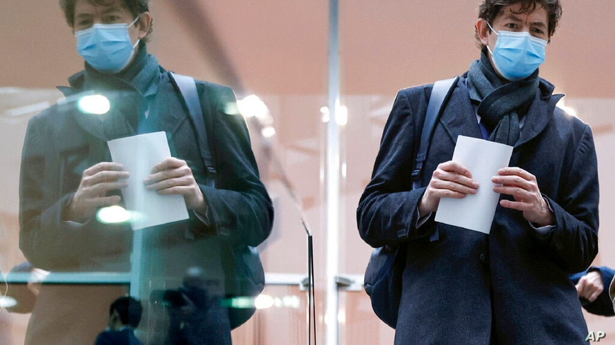 Director of the Institute for Virology at the Charite Christian Drosten is reflected in a glass as he leaves a news conference,…