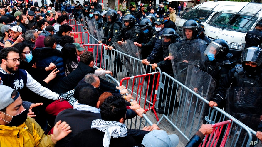 Demonstrators face police officers during a demonstration in Tunis, Saturday, Jan.23, 2021. Tunisia is extending its virus…