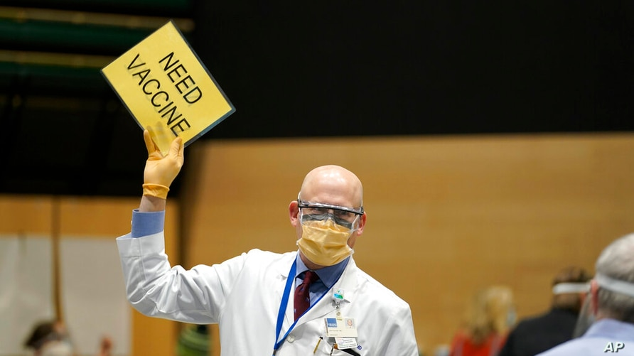 """Dr. John Corman, the chief clinical officer for Virginia Mason Franciscan Health, holds a sign that reads """"Need Vaccine"""" to…"""