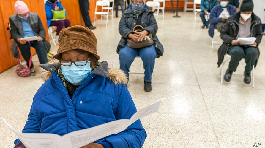 Elaine Chambers goes over a coronavirus vaccination pamphlet while resting after receiving the first dose of the vaccine at a…