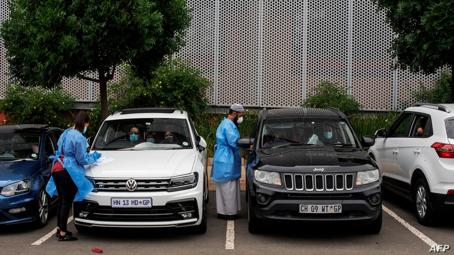 FILE - Medical technicians administer COVID-19 swab tests at a drive-through testing site at Wits University, Braamfontein, Johannesburg, South Africa, Jan. 5, 2021.