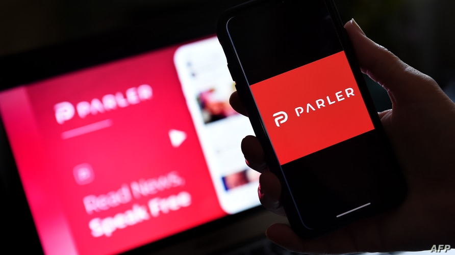 FILE - An illustration picture shows social media application logo from Parler displayed on a smartphone with its website in the background in Arlington, Virginia, July 1, 2020.