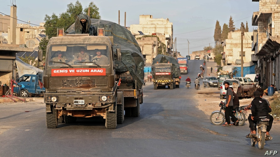 FILE - A Turkish military convoy drives through a town in Syria's northwestern Idlib province, Oct. 20, 2020. An little known Islamist group said it was behind an attack Saturday that targeted a Turkish military outpost in the province.