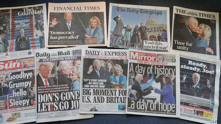 A selection of the front pages of British national newspapers on sale at a newsagent in London, Jan. 21, 2021, showing the headlines following the inauguration of President Biden.