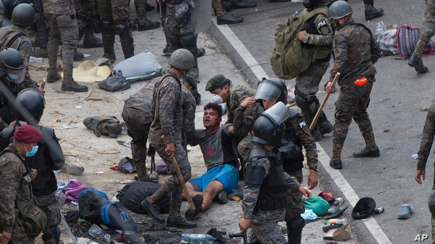 A Honduran migrant is tended to by Guatemalan soldiers after migrants clashed with them in a bid to cross the border in Vado Hondo, Guatemala, in a quest to eventually reach the United States, Jan. 17, 2021.
