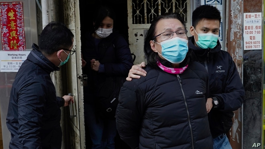District councillor and lawyer Daniel Wong Kwok-tung, center, is escorted by police outside his office in Hong Kong, Jan. 14, 2021.