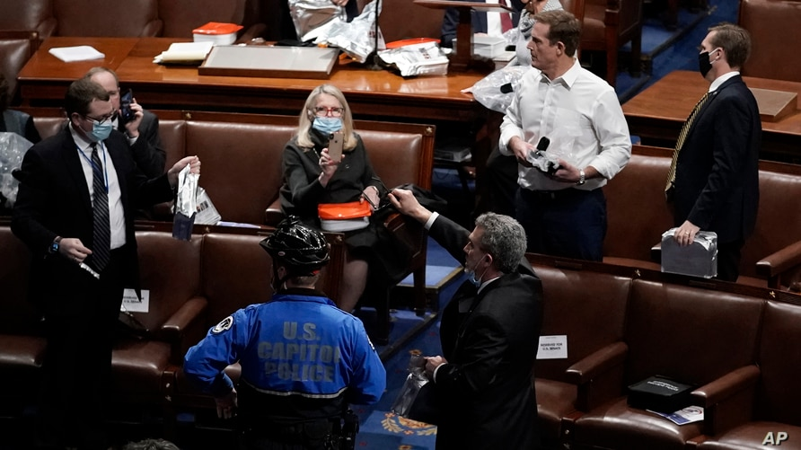 Members of Congress prepare to evacuate the floor as protesters try to break into the House Chamber at the U.S. Capitol, in Washington, Jan. 6, 2021.