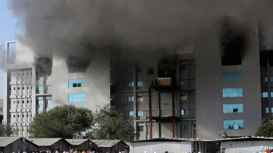 Employees leave as smoke rises from a fire at Serum Institute of India, the world's largest vaccine maker that is manufacturing the AstraZeneca/Oxford University vaccine for the coronavirus, in Pune, Jan. 21, 2021.