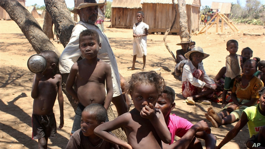 FILE - Children shelter from the sun in Ankilimarovahatsy, Madagascar, a village in the far south of the island where most children are acutely malnourished, Nov. 9, 2020.