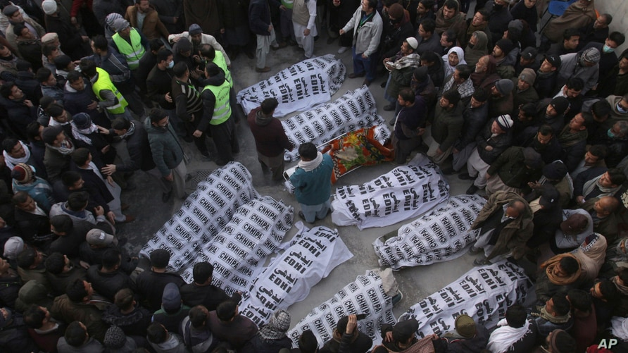 People from the Shi'ite Hazara community gather around the bodies of coal mine workers who were killed by unknown gunmen near the Machh coal field, in Quetta, Pakistan.